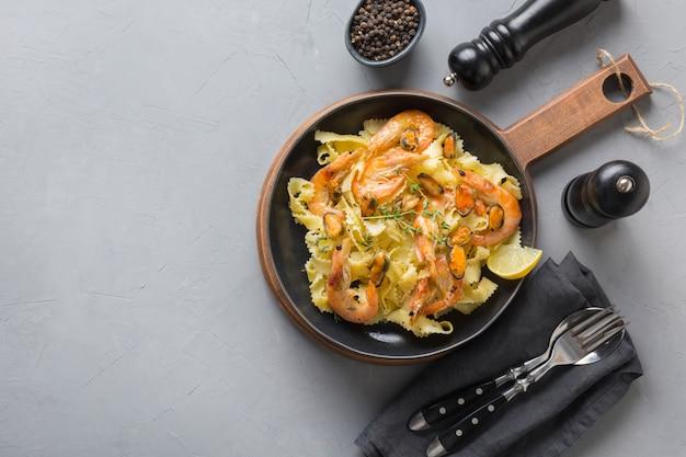 グレーのテーブルにシーフード、エビ、ムール貝のパスタレジネル。イタリアの伝統料理。