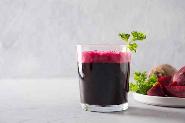 新鮮なビートジュースのガラスは、グレーのパセリを飾ります。