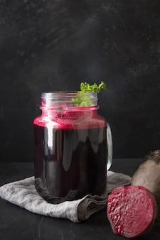 新鮮なビートジュースのガラスは、黒のパセリを飾ります。垂直方向。