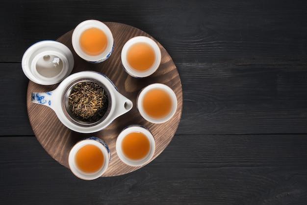 Чашки чая на темной деревянной доске. китайская чайная церемония. вид сверху.