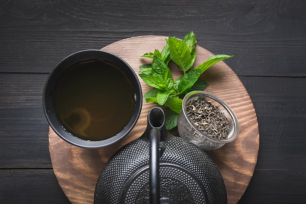 茶道。メリッサと暗い背景にやかんとお茶のカップ。中国茶のコンセプト。上からの眺め。