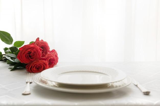 赤いバラの花束とロマンチックなテーブルの場所の設定。テキスト用のスペース。日付への招待。バレンタイン・デー。