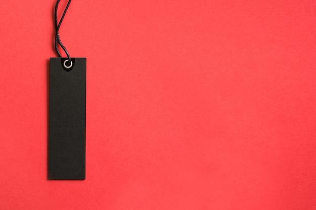 赤い背景に黒い金曜日ショッピングタグ。セール。上からの眺め。