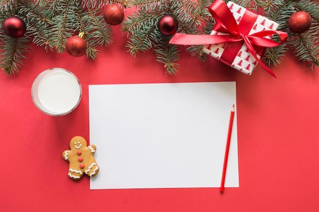 Рождественское письмо для санта-клауса с молоком, печенье, пряники на красный. вид сверху и место для вашего текста. квартира лежала.