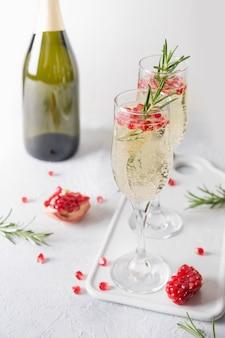 ザクロカクテルローズマリー、シャンパン、クラブソーダグレーテーブルの上。クリスマスホリデードリンク。