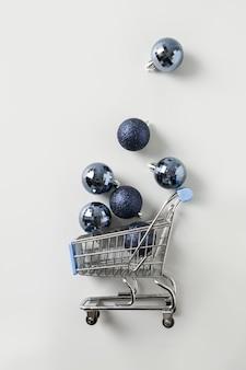 Плоская композиция из игрушечной продуктовой тележки, полной новогодних классических синих шаров
