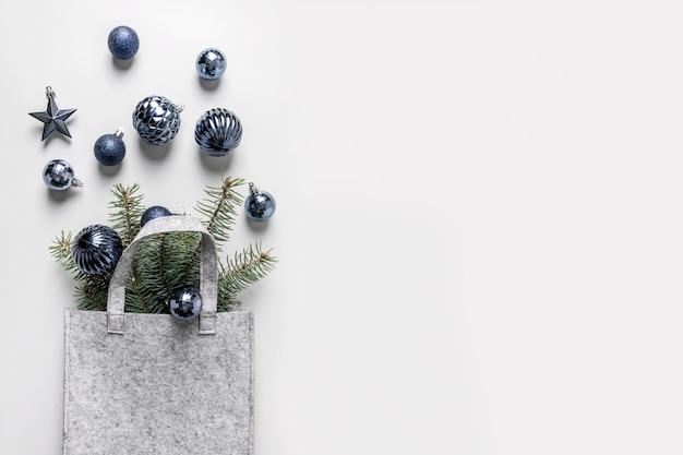 Рождественская сумка с классической синей праздничных покупок на сером фоне. рождественские торговые концепции. вид сверху, плоская планировка. пространство для текста.