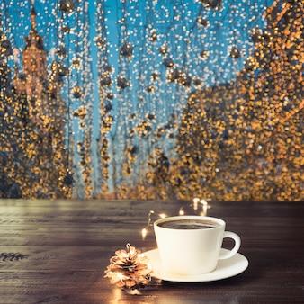 Чашка черного кофе на деревянный стол в кафе. рождественские огни и золотая гирлянда на фоне.