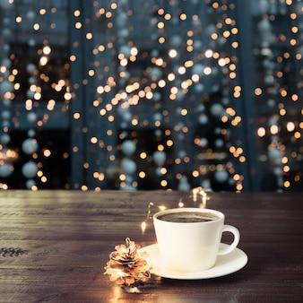 カフェの木製テーブルの上のブラックコーヒーのカップ。クリスマスライトと背景に金の花輪。