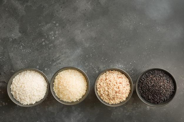 Разные сорта риса. черный рис в миску на черном. вид сверху.