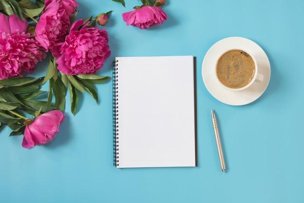 Букет из розовых цветов пиона, кофейная чашка для завтрака, пустая тетрадь, ручка на пастельной сини.