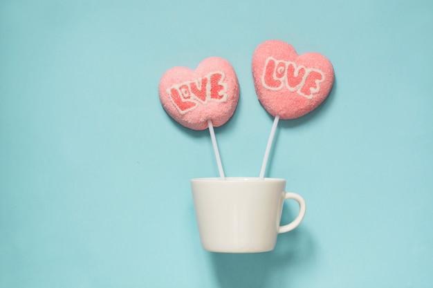Пара леденцы на палочке розовые конфеты на палочке с любовью текст на синем. концепция воздушного шара. копировать пространство