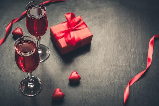 Валентинка с шампанским и конфеты сердца на черном фоне.