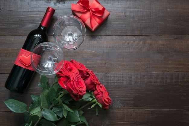 Валентинка с романтичными красными розами, винной бутылкой, сердцем и красной подарочной коробкой на деревянном столе. вид сверху с плоской планировкой.