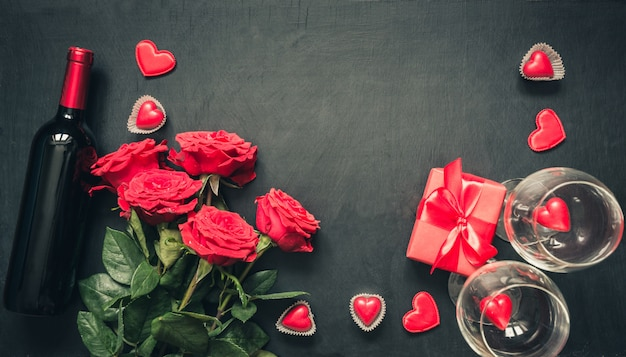 Валентинка. красные розы цветы, красное вино, сердца и подарочные коробки на черном. вид сверху. копировать пространство