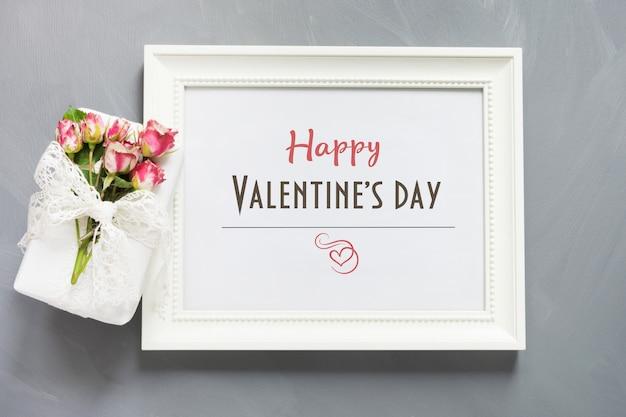 バレンタインカード。女性の贈り物とバラの白いフォトフレーム