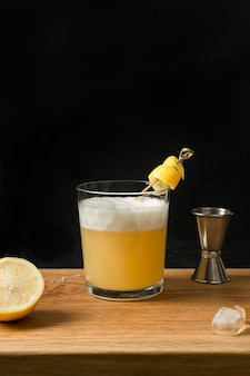 Виски кислый коктейль - бурбон с лимонным соком, сахарным сиропом и яичным белком в стакане. вертикальная ориентация.
