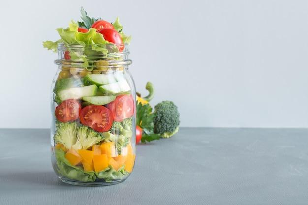 青のトマト、レタス、ブロッコリーと石工の瓶に野菜の自家製サラダ。コピースペース。仕事の昼食。きれいに食べる。