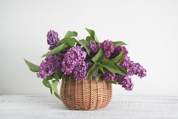白い木製のテーブルにライラックの花のバスケット