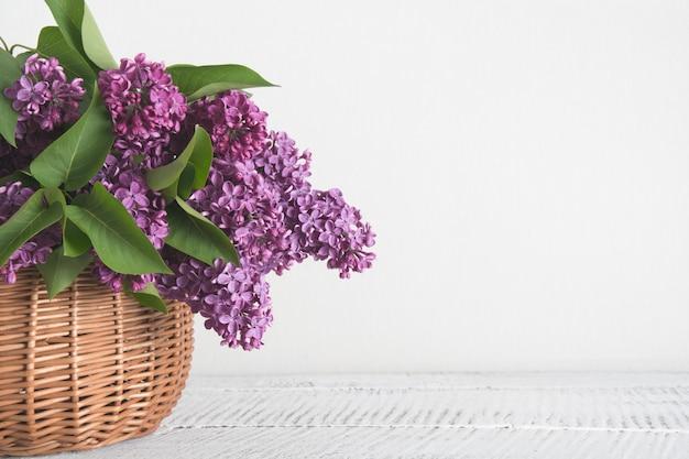 白い木製の背景にライラックの花のバスケット。ビンテージトーン。母と女性の日。