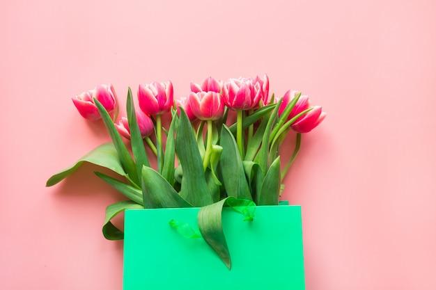 ピンクの緑の紙袋に新鮮な赤いチューリップの花。春。