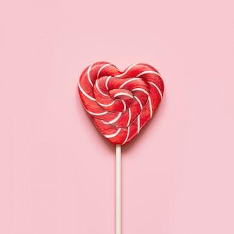 Валентинка. леденцы на палочке в виде сердца на розовом. смешная концепция.