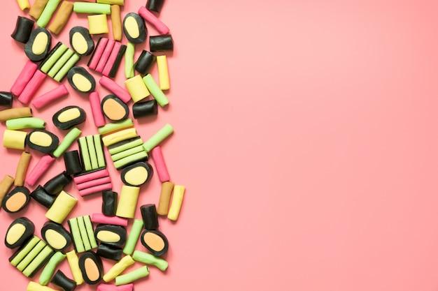 Красочные конфеты леденец и солодки на розовый.