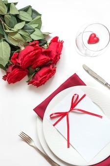 赤いバラの花束とロマンチックなテーブルセッティング。上面図。バレンタインデー。