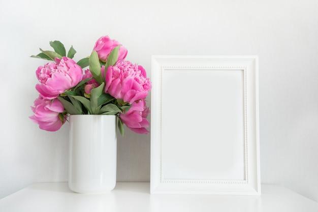 白のテキストのためのフォトフレームと花瓶にピンクの牡丹の花束。母の日。