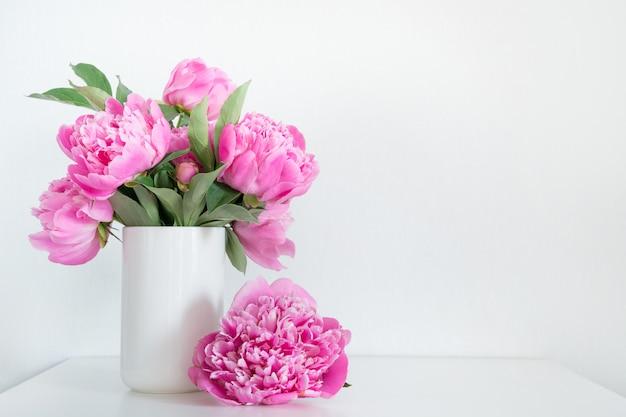 白のテキスト用の花瓶にピンクの牡丹の花束。母の日。
