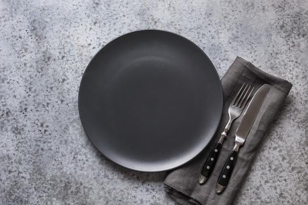 Черная плита, вилка и нож на сером каменном столе. минимальная сервировка стола.