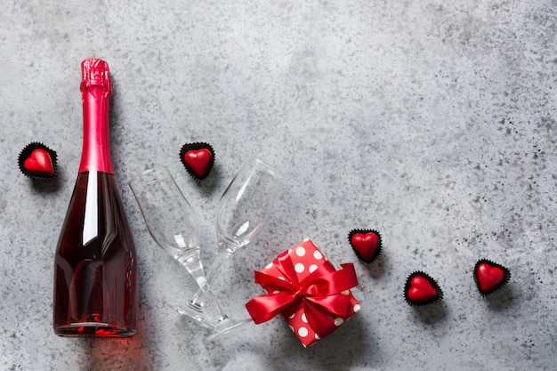 スパークリングワイン、ギフトボックス、ハート型の灰色のキャンディーのボトルとバレンタインの日グリーティングカード。ロマンチックなデートのコンセプトです。上からの眺め。