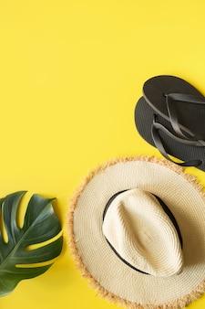 ビーチの麦わら帽子、ビーチサンダル、モンステラ。黄色の夏の休日の背景。上からの眺め。
