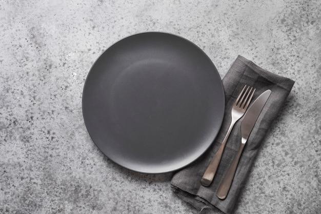 Черная плита, вилка и нож на сером каменном столе. сервировка стола