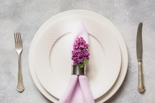 Весенняя сервировка с сиреневыми цветами, столовое серебро на светлом столе. вид сверху.