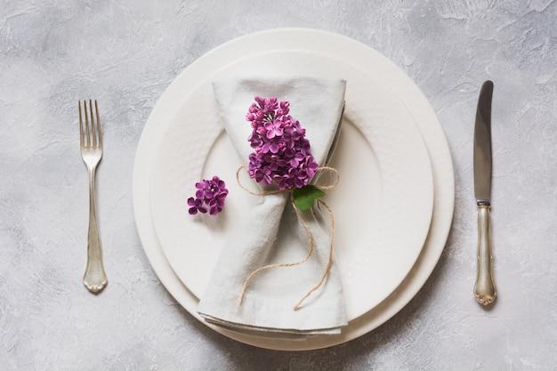 Весенняя элегантная сервировка стола с фиолетовая сирень, серебро на старинный стол. вид сверху.