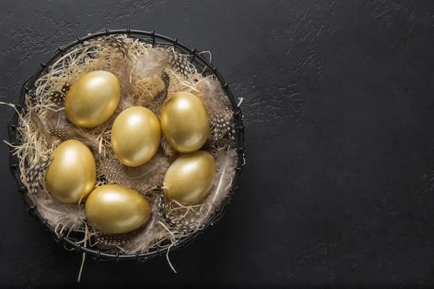 Цыпленок покрасил золотые яичка в декоративной вазе на черноте. пасхальная темная концепция. вид сверху и копирование пространства.
