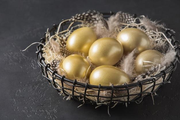 Цыпленок покрасил золотые яичка в декоративной вазе на черноте. пасхальная темная концепция.