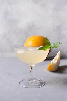 灰色の石のテーブルにワイングラスでメロンソーダ飲み物
