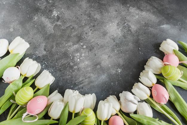 Пасхальный образец. граница белые тюльпаны, яйца, гнездо на старинный серый. вид сверху с копией пространства.