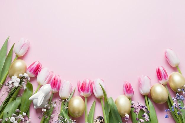 ピンクのチューリップ、黄金の卵、パステルピンクのウサギのイースターフレーム。コピースペースの平面図です。