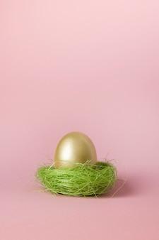 Золотое яйцо в розовом гнезде. пасха минимальный творческий состав на пастельные розовый с копией пространства. закройте с праздником пасхи. поздравительная открытка