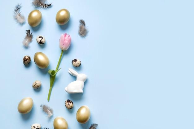 バニー、黄金の卵、青にピンクのチューリップのイースターフレーム。上面図。幸せな休日。