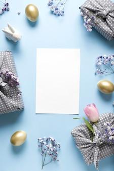 新鮮な花、黄金の卵、プレゼント、青のバニーのイースターフレーム。コピースペースの平面図です。幸せなイースター休暇。垂直グリーティングカード。