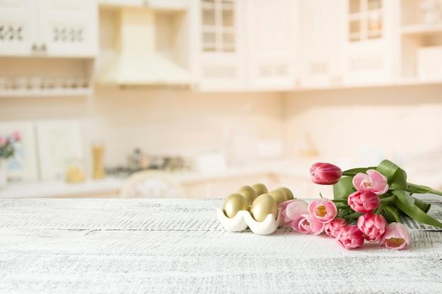 イースターエッグ、白いキッチンテーブルの上のチューリップ。春の組成物。デザインのためのスペース。