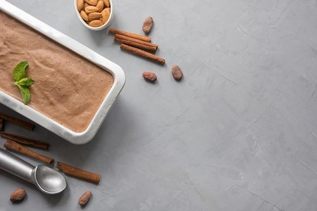 Банановый шоколад домашнее мороженое в контейнере с кофе в зернах на серый. место для текста. вид сверху.