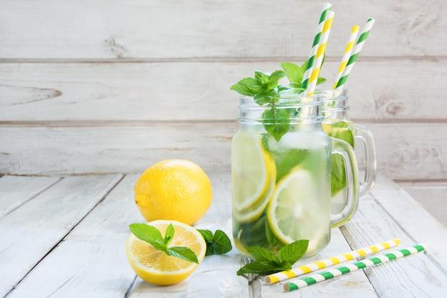 夏のさわやかなデトックスカクテル。レモン、ミント、白い木の板の石工の瓶に氷と水します。素朴なスタイル。
