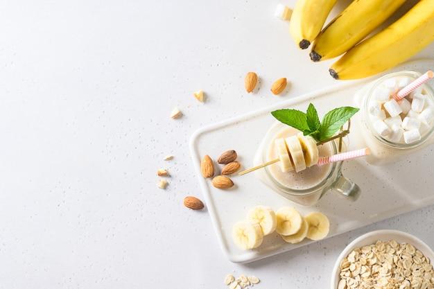 Банановый молочный коктейль в мейсон банку на белой доске. вертикальный формат