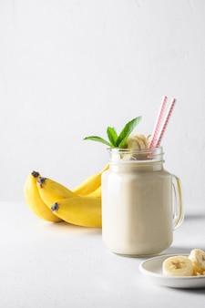 Банановый молочный коктейль на белой доске. вертикальный формат