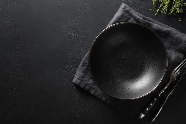 Черная тарелка украшена веточкой тимьяна на черном. вид сверху.